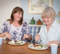 Home Instead Senior Care Wembley CAREGiver and client sit and eat meal