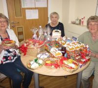3 watling court residents and their table of goods for the fundraiser