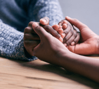 Carer and service user holding hands