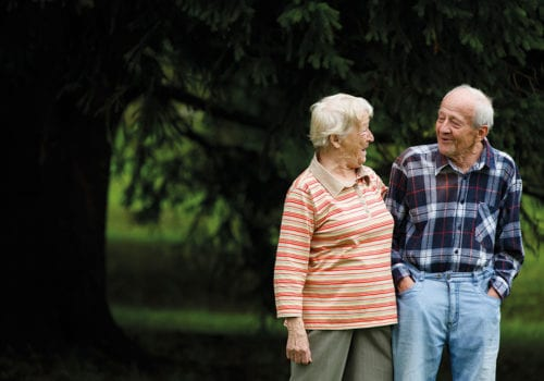 happy elderly couple stroll outside
