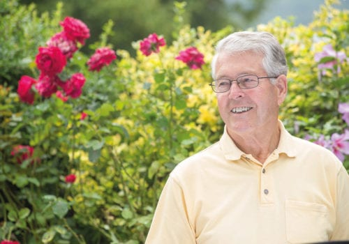 older man in garden smiles at camera