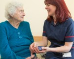 St Martin's resident and carer sit next to each other