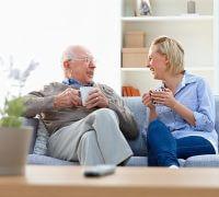 Promedica24 Senior man and female carer enjoying coffee in living room