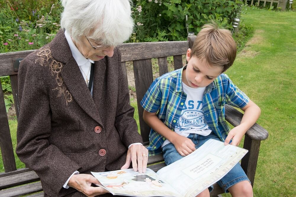 Intergenerational reading taking place in the garden