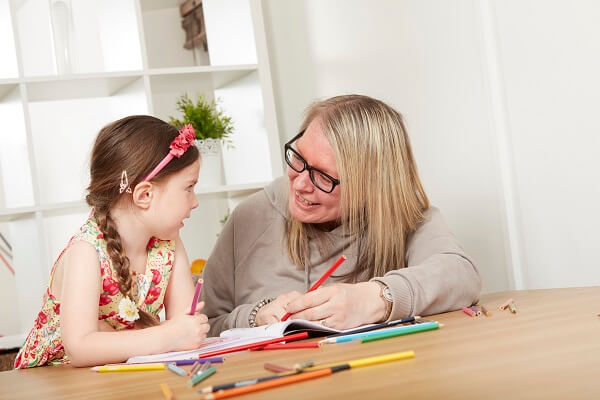 child and care worker colouring at table