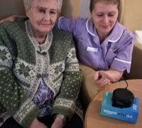 carer and resident of peterlee care home with an amazon alexa device explore new technology for care home residents