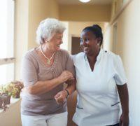 Adada Care carer and service user stroll down a corridor
