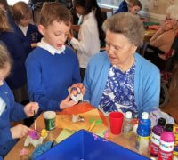 residents and school pupils bridging the generation gap in an easter egg decorating session