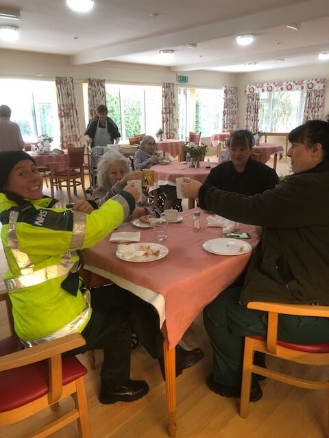 Paramedics enjoying care home residents kindness sharing in bacon sandwiches and hot drinks