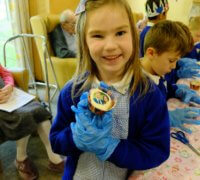 pupil displays a cake from the tea party where care home residents and pupils celebrate royal wedding