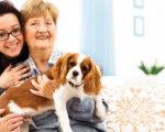 Happy customer of Promedica24 East Surrey, Croydon and Bromley cuddling pet dog
