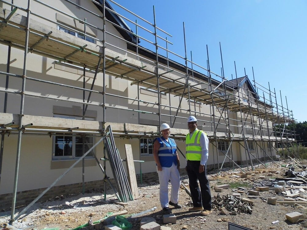 Gail Fielding with Raj Singh standing outside the construction site of new specialist dementia care home in west sussex