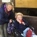 Smiling care home resident in wheelchair meets the horses during an animal therapy trip