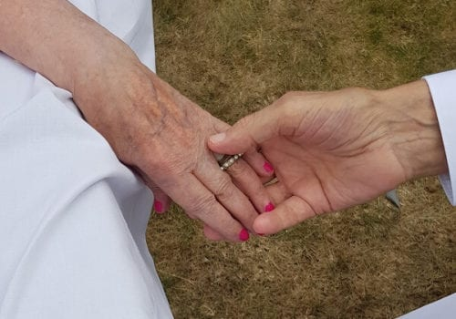 couple hold hands at their second wedding in dementia care home
