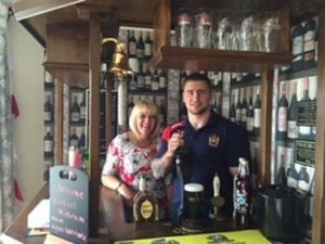 Wigan Warrior, Michael McIlorum, pulls a pint with Ash Tree House Home Manager, Kathryn Disley