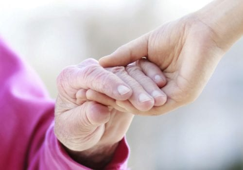 older and younger person holding hands
