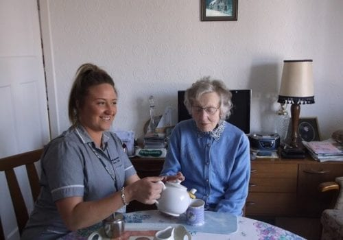 Independant Care Link Carer and Client havingcup of tea in home