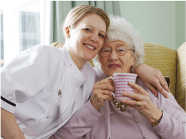 Elderly lady with a tea and eniola care carer smile for camera