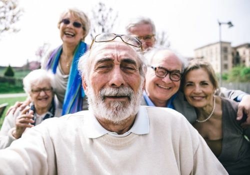 Group of happy sociable older people smile for the camera