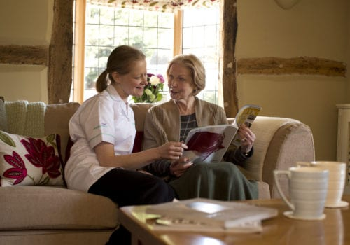 Helping Hands Fareham carer talks with service user in living room