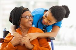 MK Nursing care worker smiling at smiling older lady in wheelchair