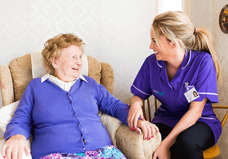 Surecare Harrow and Watford carer sits alongside service user in armchair