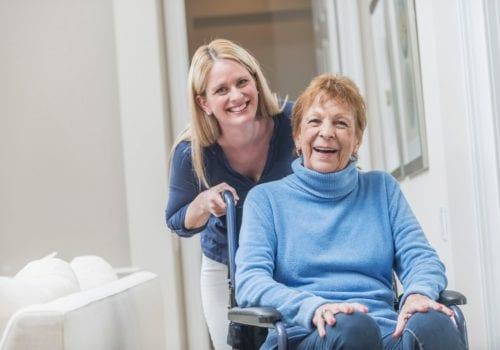 A senior woman sitting in a wheelchair at home with a caregiver standing behind her. They are looking at the camera, smiling. The caregiver could be her daughter or a home healthcare worker.