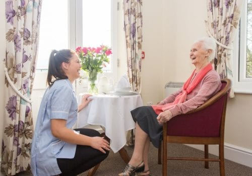 Alfriston court carer kneels down alongside a resident in sitting area
