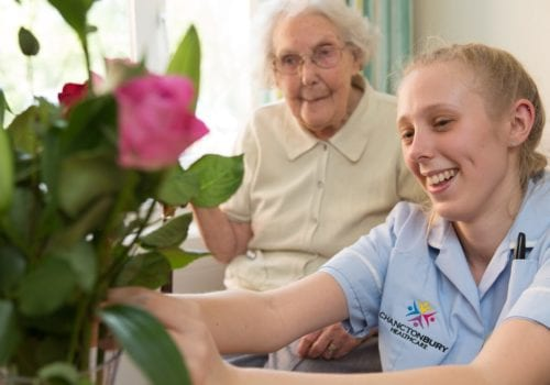 oaklands court resident watches as carer arranges flowers for her