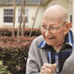 Elderly man smiles at camera in garden