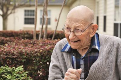 Elderly man smiles at camera in garden