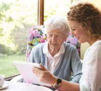carer and elderly lady looking at iPad
