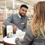 talking tables, sainsbury's staff member and customer chat over coffee