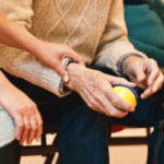 elderly man and carer holding hands