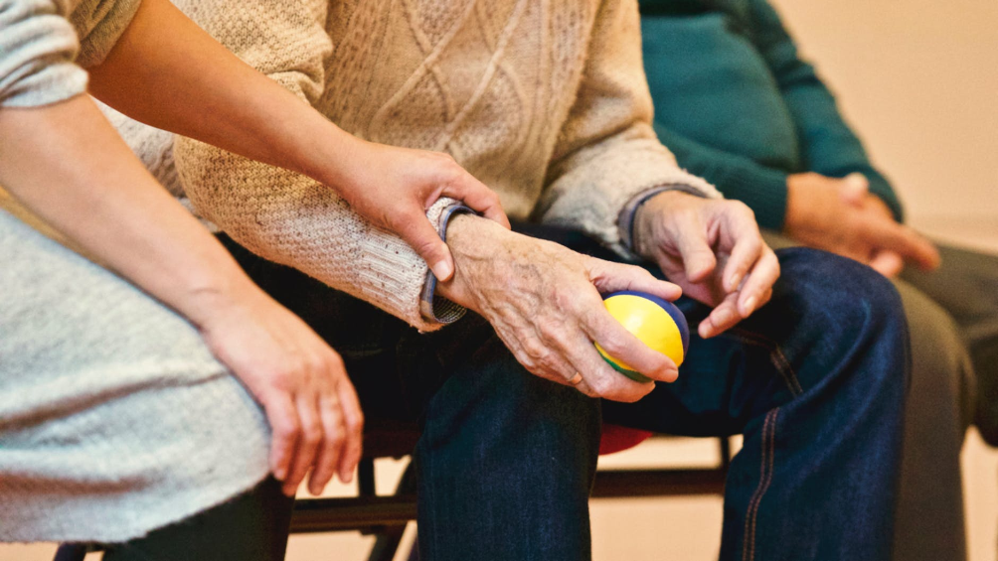 elderly man and carer holding hands
