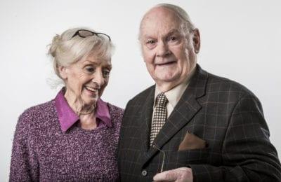 elderly couple smile for camera