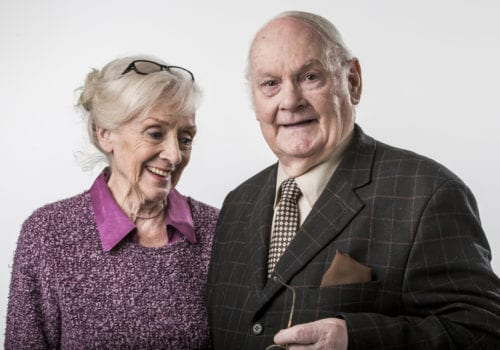 elderly couple smile for camera