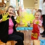 carehome residents and nursery group enjoy hand painting as part of Intergenerational fun