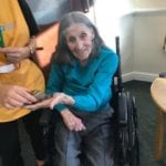 resident holds a giant snail at animal therapy session