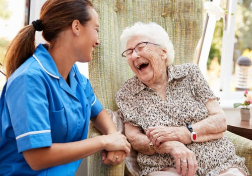 elderly lady laughs out loud with carer