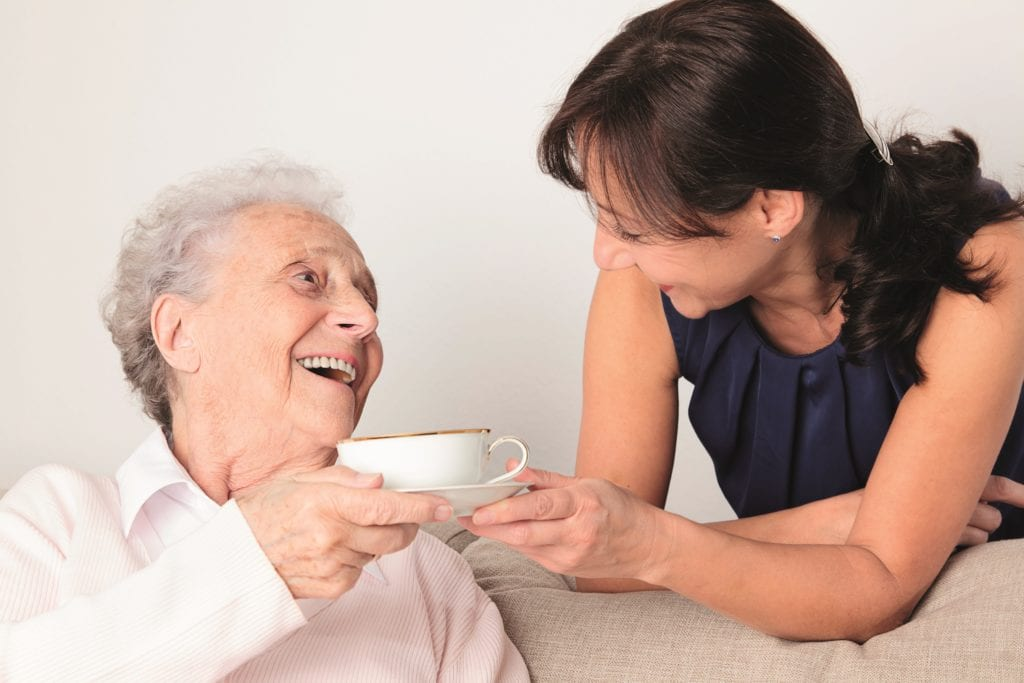 Elderly lady take s a cup of tea from out stretched hand of daughter