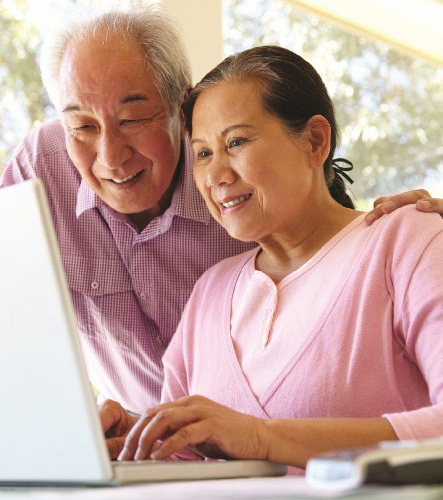 Senior Taiwanese couple researching dementia on laptop