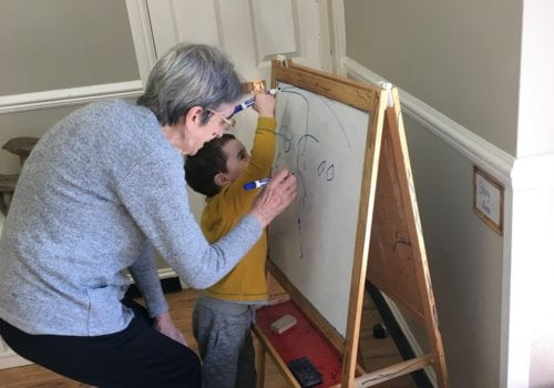 elderly lady and toddler drawing on easel