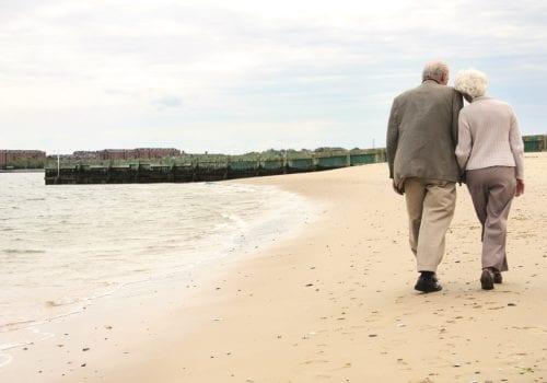 elderly couple walk down deserted beach