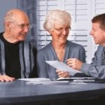 elderly couple sit with solicitor at table