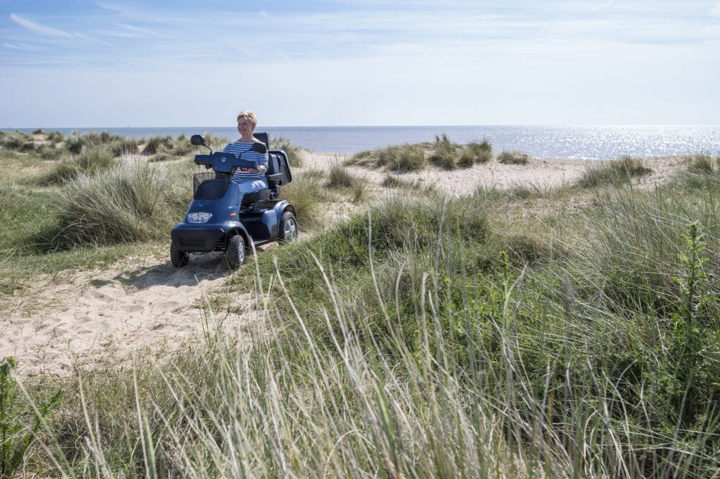 lady drives mobility scooter across sand dunes
