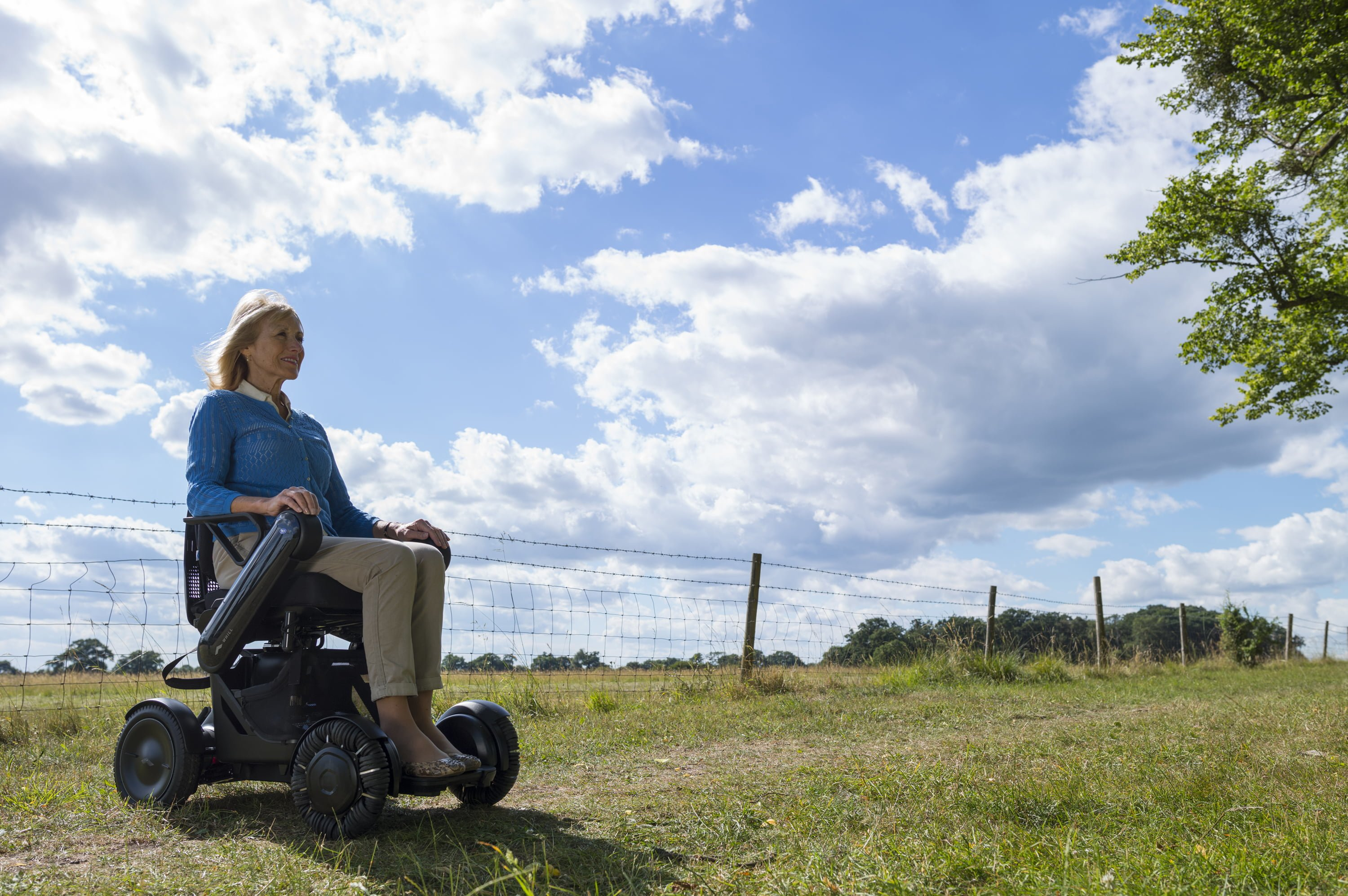 lady using a TGA mobility wheelchair looking out across open countryside
