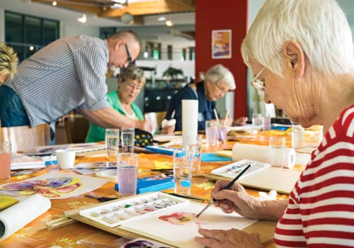 Woman in striped red and white shirt working on canvas while painting with brush at table with other residents