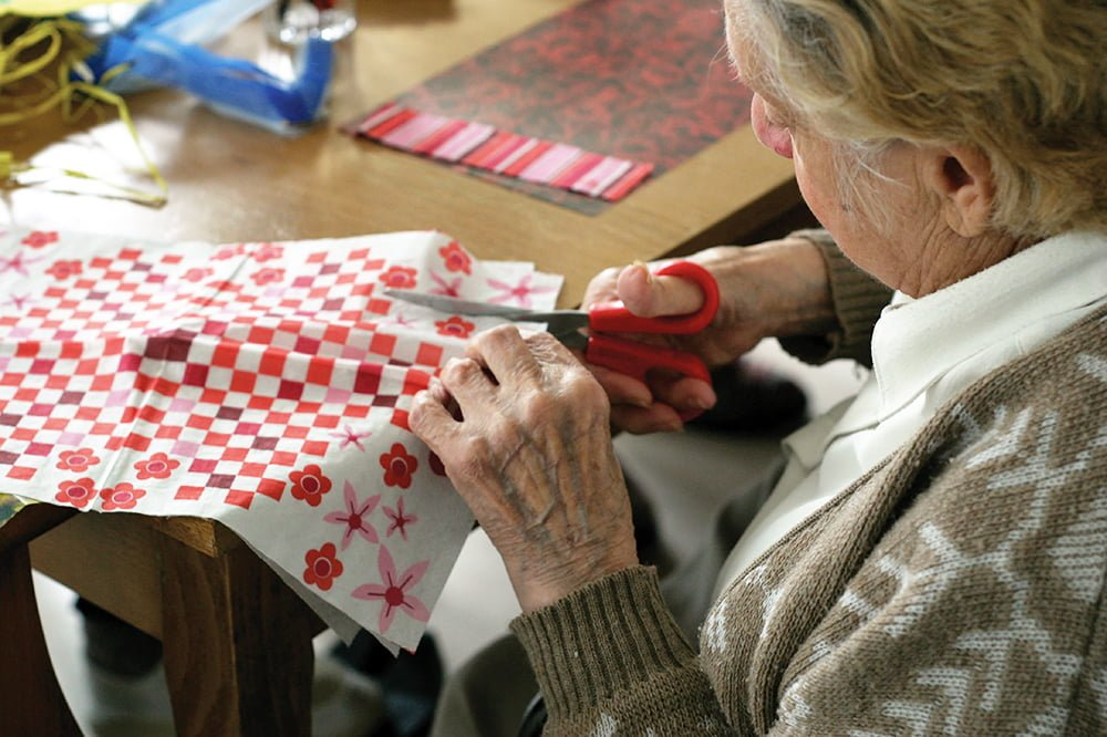 Elderly person sewing as part of a group