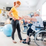 Older lady in wheelchair doing exercise with personal trainer